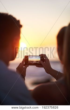 Couple using mobile phone to photograph sunset, romantic beautiful seaside scenary golden light