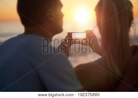 Couple watching the sunset on the horizon, taking photo on mobile phone beautiful seaside scenary golden light sun flare