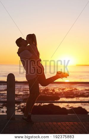 Silhouette of couple kissing romantically while watching sunset on the horizon, beautiful seaside scenary golden light sun flare