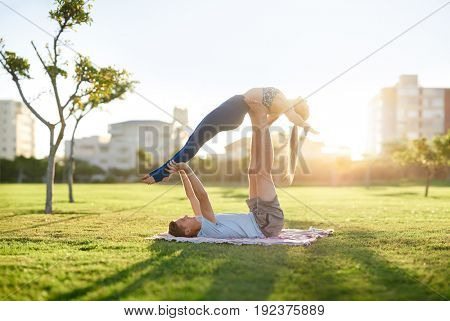 Active healthy couple doing acroyoga in the park with sun flare, trust bonding loving relationship exercise together