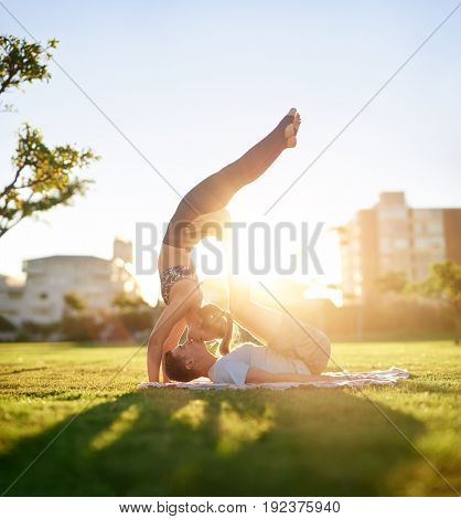 Active flexible couple doing acro yoga on the grass at sunset, trust bonding loving relationship exercise together