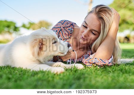 Smiling woman with puppy in the park, loving moment between pet and owner