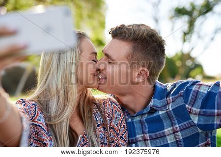 Happy couple in love using mobile phone smartphone to take kissing selfie, affectionate and loving