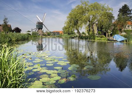 Windmill on the rural river Graafstroom in the Dutch village Bleskensgraaf