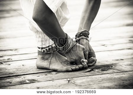 closeup of woman feet and hands in yoga postion lot of bracelets and rings outdoor shot on wooden pontoon  black and white