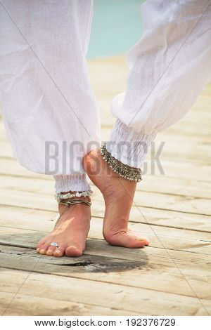 closeup of young woman barefoot legs in white clothes and anklets boho summer fashion style on wooden pontoone by the lake