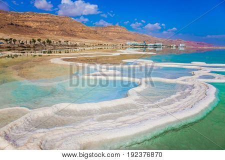 The evaporated salt is precipitated by picturesque stripes in shallow water. Reduced water in the very salty Dead Sea, Israel. The concept of medical and ecological tourism