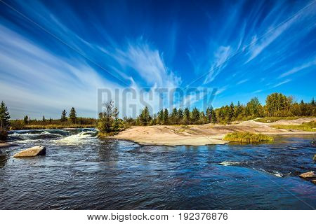 Thin cirrus clouds and foam water rapids on the Winnipeg River. Trend of travel