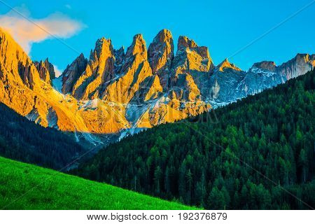 The Dolomites. Magnificent serrated cliffs illuminate the summer sunset. The concept of eco-tourism in Tirol