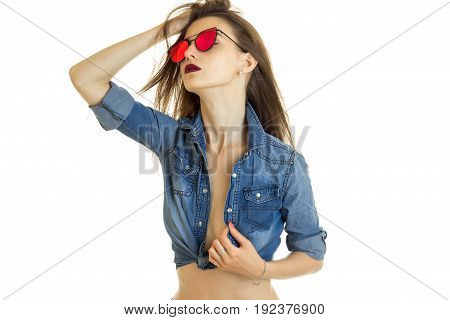 Sensual lady in sunglasses and jeans shirt without bra under isolated on white background