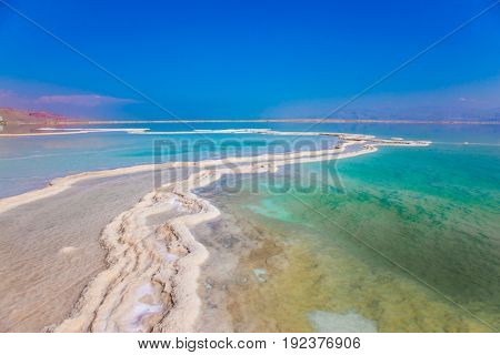 Very salty water glows with turquoise light. The Dead Sea, Israel. The evaporated salt has developed into fantastic patterns. The concept of ecological and medical tourism