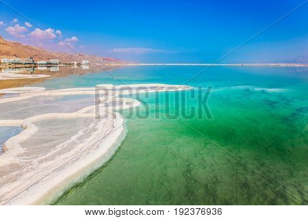 Very salty water glows with turquoise light. Reduced water in the Dead Sea. The evaporated salt has developed into fantastic patterns. The concept of ecological and medical tourism