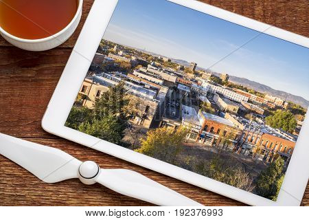 reviewing aerial pictures of Fort Collins downtown on a digital tablet with a cup of tea