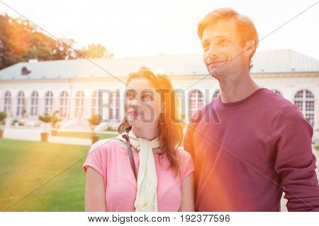 Thoughtful tourist couple smiling outdoors