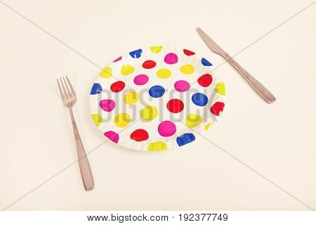 Multicolored plate with polka dots and cutlery over white background