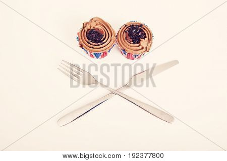 Union Jack chocolate cupcakes with fork and knife against white background