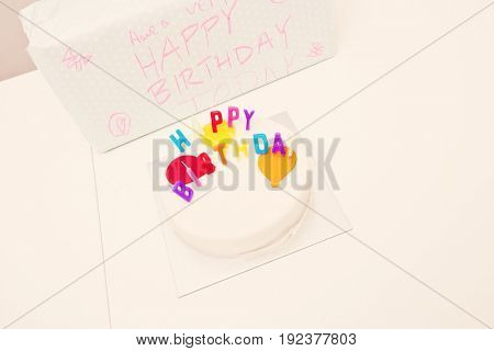 High angle view of birthday cake and gift on table