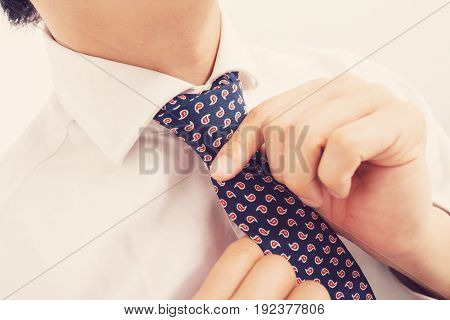 Midsection of mid adult businessman adjusting tie