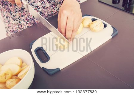 Midsection of man cutting potato at kitchen counter