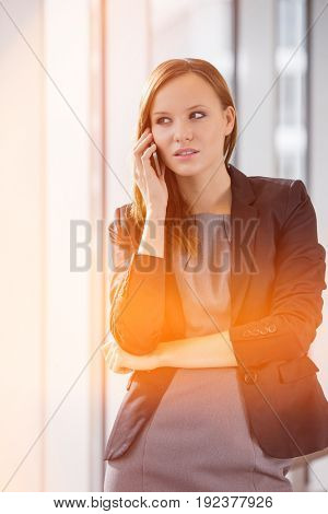 Beautiful businesswoman using cell phone in office