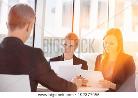 Business people discussing paperwork in office cafeteria