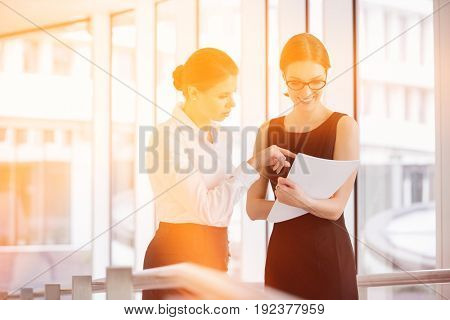 Businesswomen discussing over documents in office