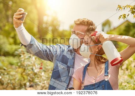 Male and female professional gardeners posing for selfie with sprayers and respirators while fertilizing plants in hothouse.