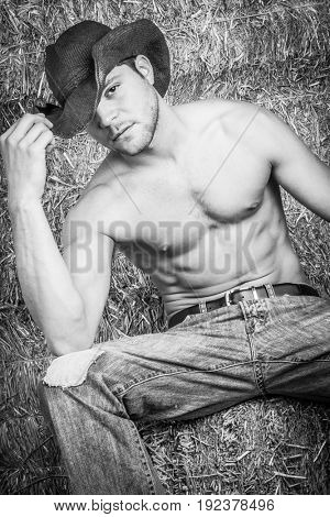 Country cowboy man sitting on hay bales