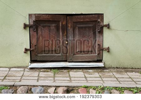 Old ancient window closed with wooden shutters in wall of medieval hose in Vilnius, Lithuania.