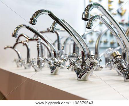 Kitchen faucets on shelf closeup, plumbing shop
