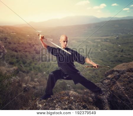 Wushu master with sword, meditation on mountain