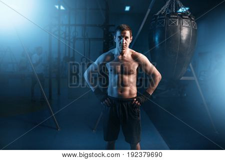 Portrait of athletic boxer in black bandages