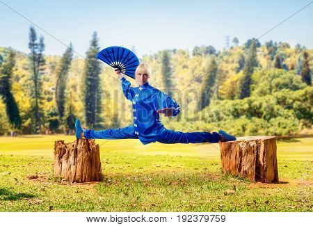 Female wushu master with fan sits on a twine