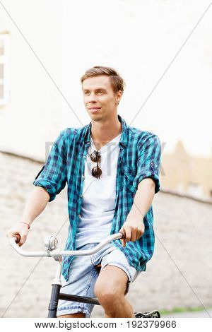 Handsome hipster riding a bicycle in old town. Traveling, holiday, vacation concept.