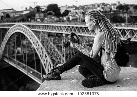 Young woman with dreadlocks, pictures of on camera, old city, Porto, Portugal. Black-and-white photo.