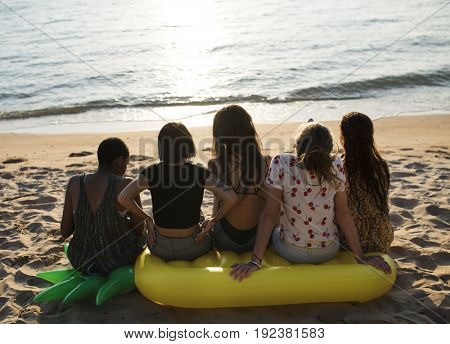 Group of diverse women sitting at the beach together