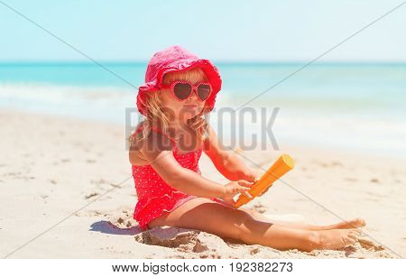 sun protection concept - little girl with suncream on beach