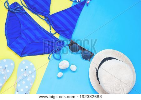 Creative flat lay of blue color bikini and woman accessories Summer vacation concept