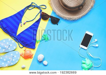 Flat lay of woman swimwear and accessories with smartphone Summer concept