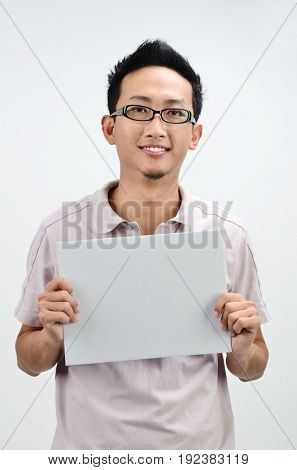 Casual Asian male displaying a grey empty card, standing isolated on grey background.