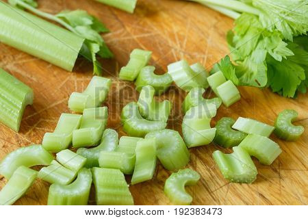 Fresh Celery Cut Into Small Pieces On Wooden Board
