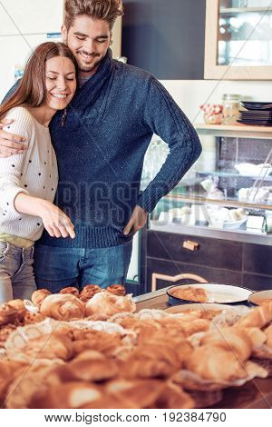 Portrait of happy young couple shopping at bakery shop.Food sale, consumerism and people concept.