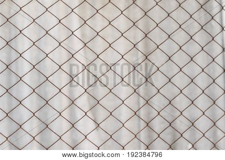 Texture of an old rusty mesh. Metal net on white background