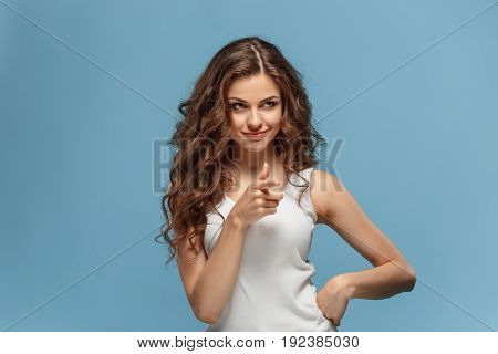 The young woman's portrait with happy emotions on blue background pointing at camera