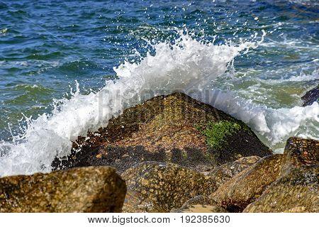 Wave crashing on the rocks of Red Beach beach at Urca Rio de Janeiro