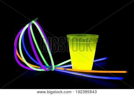 Yellow fluorescent glass and ball made with glow sticks neon light on back background. variation of different colored chem lights