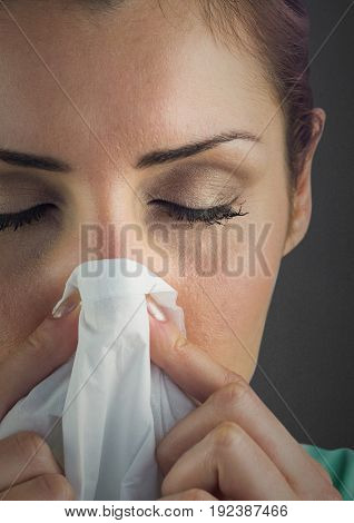 Digital composite of Close up of woman blowing nose against grey wall