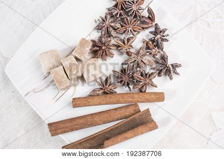 Cinnamon sticks anise stars and pieces of brown sugar lie on a white wart saucer on a white lace background