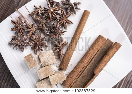 Three cinnamon sticks anise stars and pieces of brown sugar lie on a white square saucer on a brown wooden background top view