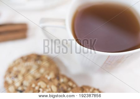 White cup with tea and homemade phtness cookies with cereals in a defocus on a light background
